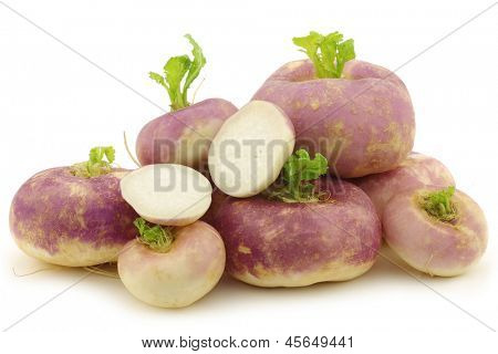 freshly harvested spring turnip (Brassica rapa) and a cut one on a white background