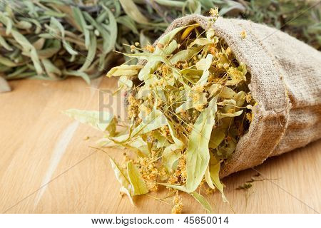 Linden Flowers In Canvas Bag On Wooden Table, Herbal Medicine