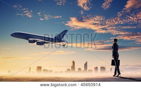 Imagem de mulher de negócios segurando a mala a olhar para um avião no céu