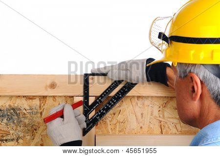 Closeup of a carpenter using a framing square to mark lines on the studs of a wall. The man wearing a work shirt, gloves and a hard hat. Shallow focus with the focus on the hand and tool.