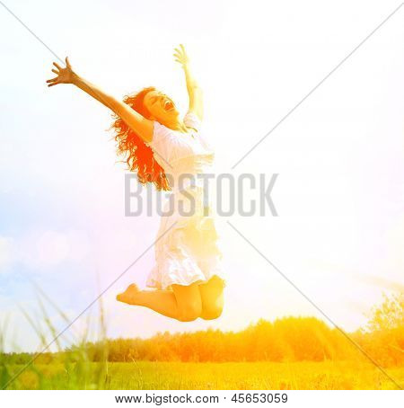 Happy Young Woman Jumping over Sun. Beauty Girl Having Fun Outdoor. Freedom Concept. Nature. Green Field