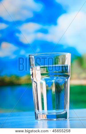 glass of the water on the beach