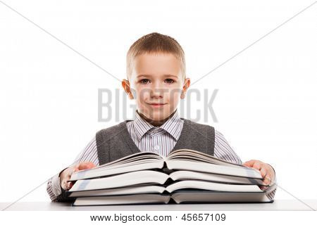 Little smiling child boy reading education books at desk
