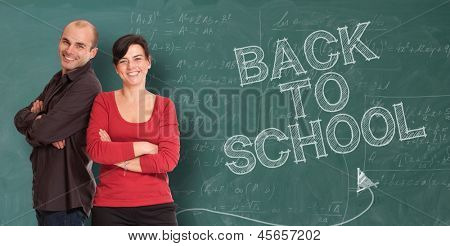 Smiling man and woman standing by a chalkboard with the words back to school