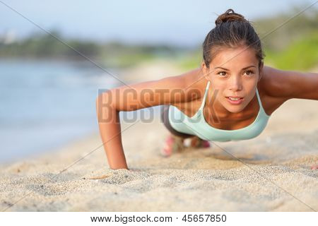 Push-ups fitness woman doing pushups outside on beach. Fit female sport model girl training crossfit outdoors. Mixed race Asian Caucasian athlete in her 20s.