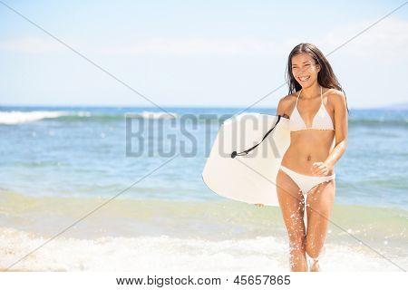 Surfer girl - body surfing beach woman laughing having fun bodyboarding under sun and blue sky during summer travel vacation on Kaanapali beach, Maui, Hawaii, USA. Mixed race Asian bikini babe.