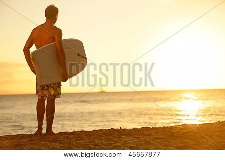 Surfer man on beach at sunset holding bodyboard. Fit male body surfer guy enjoying sunset and bodyboarding on summer holidays vacation on tropical beach. Fitness model, Kaanapali beach, Maui, Hawaii.