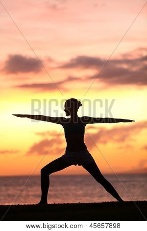 Yoga woman training and meditating in warrior pose outside by beach at sunrise or sunset. Female yoga instructor working out training in serene ocean landscape. Silhouette of woman model against sun.