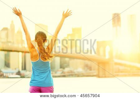 Happy cheering woman in New York City enjoying view and sun on Brooklyn Bridge. Fit female fitness runner joyful and excited after running.