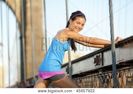 Runner stretching after running on Brooklyn Bridge, New York City, Manhattan. Fit woman fitness model portrait smiling happy after outdoor summer workout. Beautiful mixed race Asian Caucasian model.