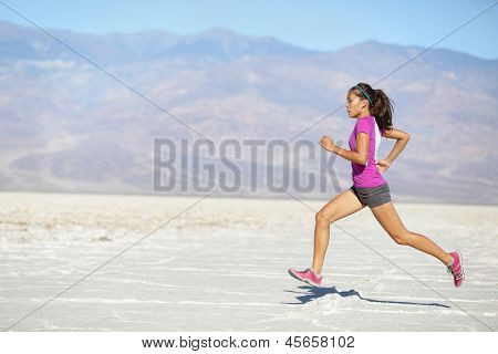 Runner woman running and sprinting on trail run in desert. Female sport fitness athlete in high speed sprint in amazing desert landscape outside. Mixed race Asian Caucasian fit sports model sprinter.