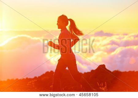 Running - woman runner jogging at sunset. Fitness spot girl training in sunny sunshine with flare and sun glow. Aspirations workout image with asian jogger.
