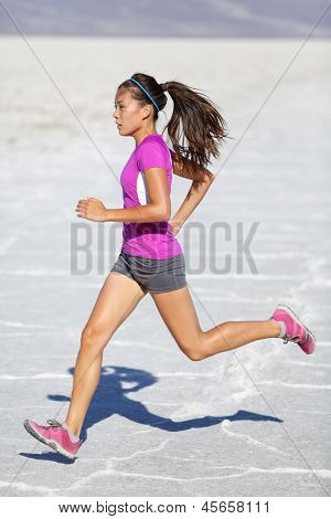 Running woman - runner sprinting on trail run in desert nature landscape. Female sport fitness athlete in high speed sprint in amazing desert landscape outside. Multiracial fit sports model sprinter.