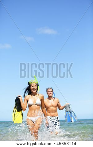 Travel beach vacation people. Happy couple having fun in ocean water on tropical beach with snorkeling fins equipment running laughing together. Summer sun image with interracial couple, man and woman