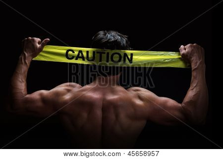 Attractive young man flexes his muscles whilst holding a caution tape behind his head. Low key portrait on black background.