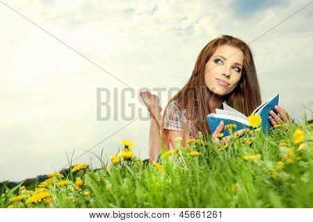 Beautiful girl lies on meadow and reads the boo