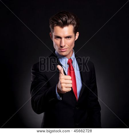 portrait of a young business man standing against a black background and showing thumbs up sign while looking at the camera