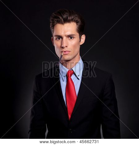 portrait of a young business man standing against a black background with an unlit cigarette in his mouth while looking at the camera