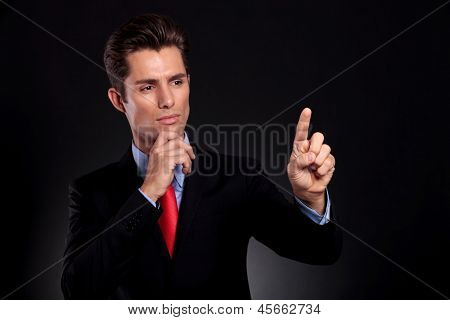 portrait of a young business man standing against a black background and pushing an imaginary button on a screen while looking at it with a pensive expression