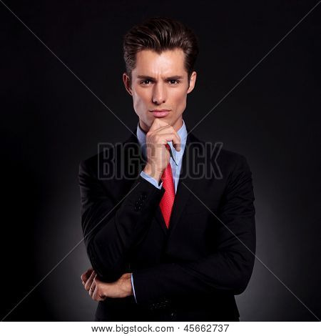 portrait of a young business man standing against a black background with a pensive expression with his hand on his chin and looking at the camera