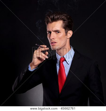 portrait of a young business man standing against a black background and preparing to take a smoke out of his cigarette while looking at the camera