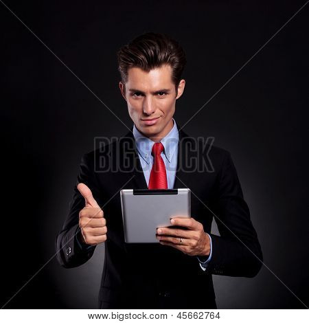 portrait of a young business man standing against a black background holding a tablet and showing the thumbs up sign while smiling to the camera