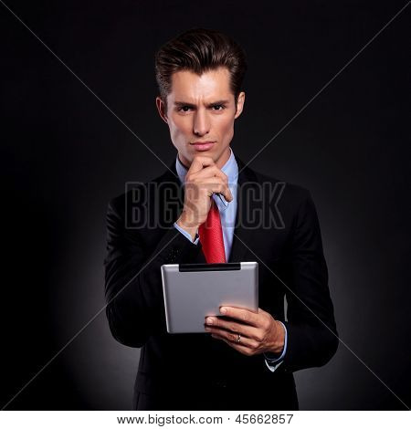 portrait of a young business man standing with his hand on his chin against a black background while holding a tablet and lookong pensively at the camera