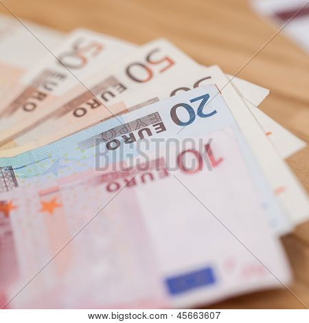 Heap of different euro banknotes on a wooden table