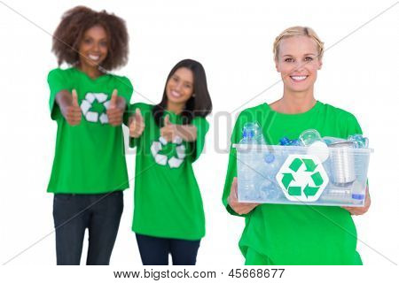 Smiling activist holding recycling box with friends giving thumbs up behind
