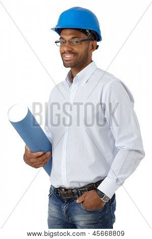 Portrait of smiling ethnic engineer in hardhat holding floor plan, cutout on white.
