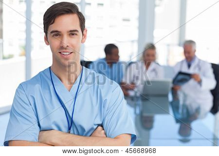 Young doctor with arms crossed standing in front of his team