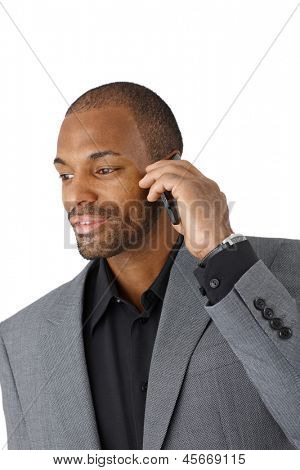 Smiling black businessman in smart suit on mobile phone call, cutout on white.
