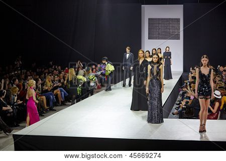 MOSCOW - APR 4: Models walk at podium in Gostiny Dvor and spectators give flowers to Valentin Yudashkin after his show at opening of 27th Volvo Fashion Week, April 4, 2012, Moscow, Russia.