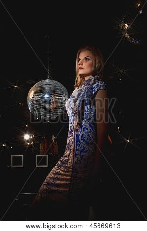 Close-up face of young blonde woman disco mirror ball