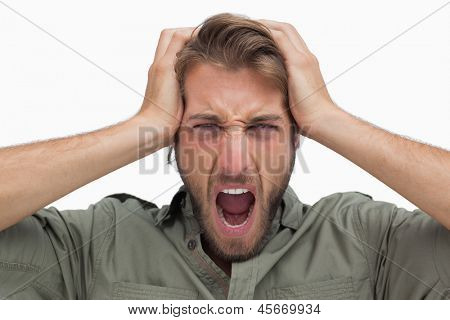 Furious man with hands on head on white background