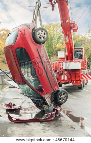 MOSCOW - OCT 9: Close-up large red rescue vehicle helps injured Peugeot 206 in car crash in the river Yauza on October 9, 2011 in Moscow, Russia.
