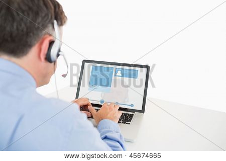 Call center worker viewing social media profile on laptop sitting at desk