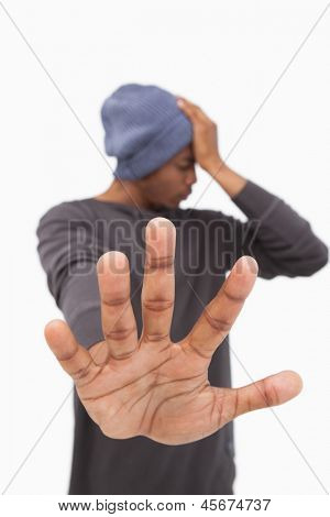 Man in beanie hat holding hand out to stop on white background
