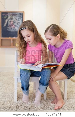 Two girls are sitting in the game room on the chairs and read a book