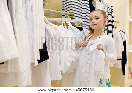 Little girl tries on white blouse in clothing store