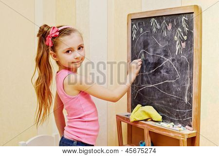 Half-length portrait of little girl who draws with chalk on blackboard