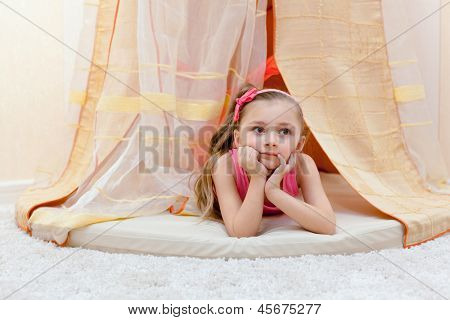 Little girl lies on her stomach, propping thoughtful face with her hands under baldachin