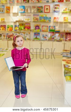 Little girl stands looking thoughtful holding open book in book department at store