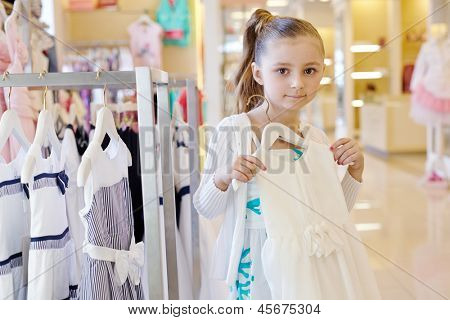 Little girl stands holding hanger with white gown in clothing store