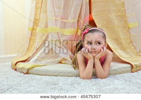 Little girl lies on her stomach, propping face with her hands under baldachin