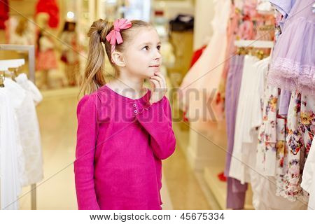 Little girl looks, touching chin with fingers, upon dresses hanging at stand in clothing store