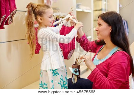 Mother and her little daughter choose swimsuit for girl in clothing store