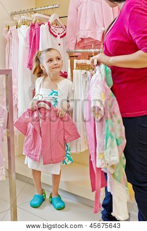 Little girl stands holding hanger with pink jacket and looks at mother who talks her something