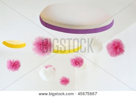 Stylish ceiling with dangling pink and white pom-poms in kids room.