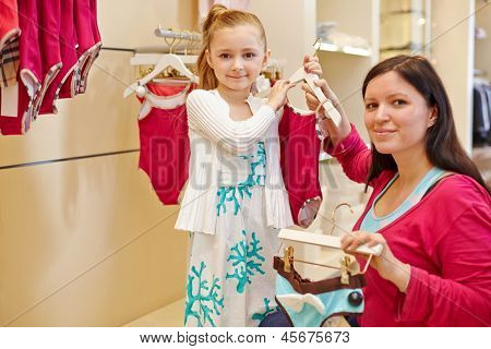 Mother and little daughter choose swimsuit, focus on girl